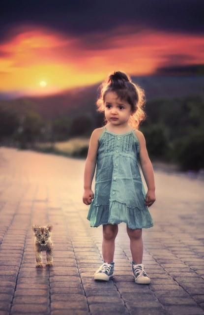 ライオンの赤ちゃんと並ぶ女の子