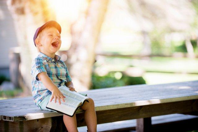 本を読んで爆笑する男の子
