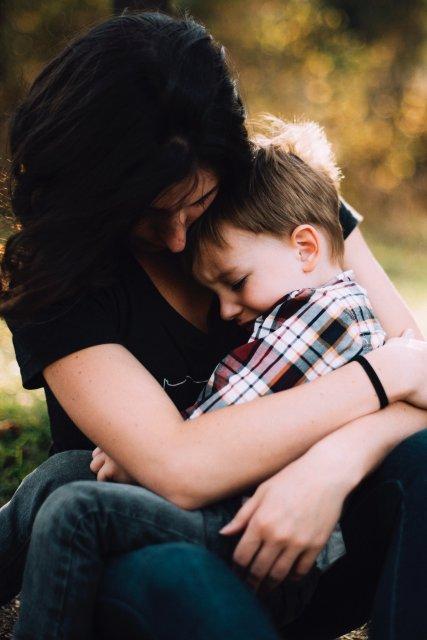 子供をぎゅっと抱きしめている母